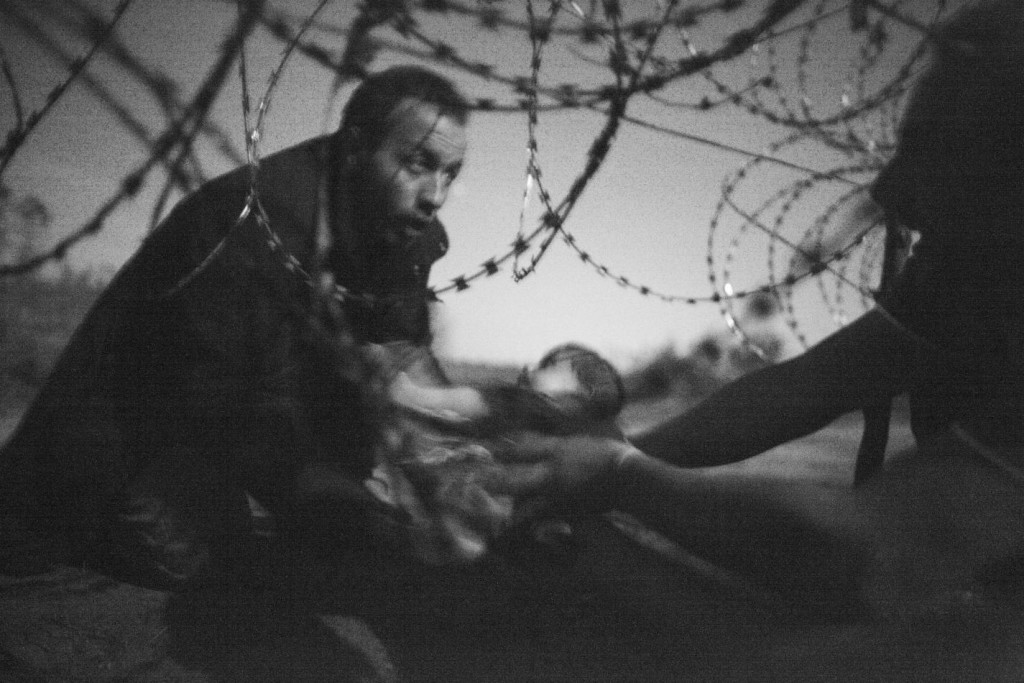 A man passes a baby through the fence at the Hungarian-Serbian border in Röszke, Hungary, 28 August 2015